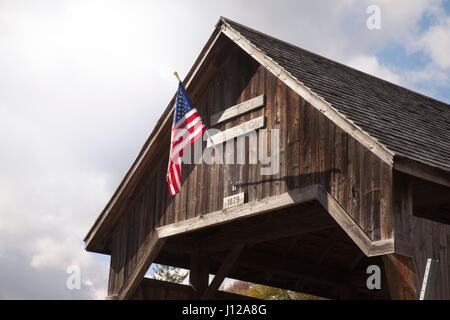 Antique covered wooden bridge with an American flag in Vermont, countryside - Stock Image