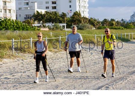 Miami Beach Florida Nordic walking pole ski fitness sand woman man exercise overweight - Stock Image