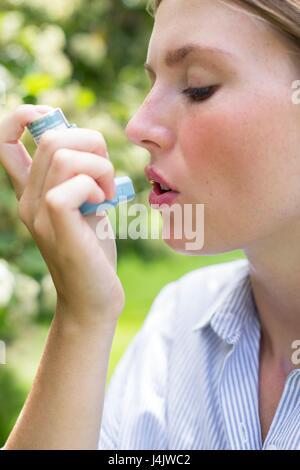 MODEL RELEASED. Young woman using inhaler. - Stock-Bilder