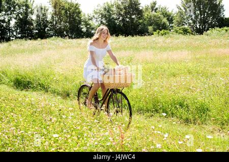 MODEL RELEASED. Young woman riding bicycle in field. - Stock-Bilder