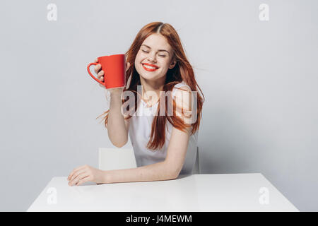 Caucasian woman sitting at windy table holding red cup - Stock-Bilder