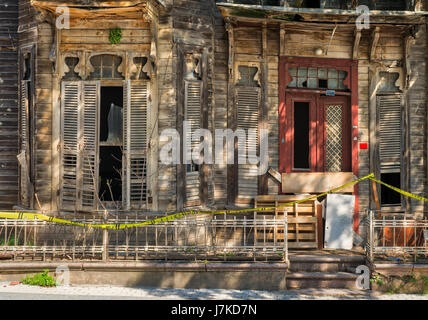 Vintage door and window on abandoned wooden house with small balcony and rusted metal fence on street level - Stock Image
