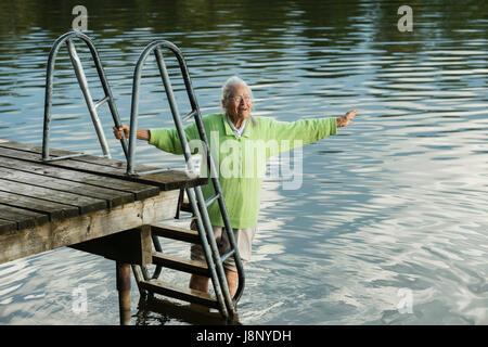 Woman by pier, wading in water - Stock-Bilder