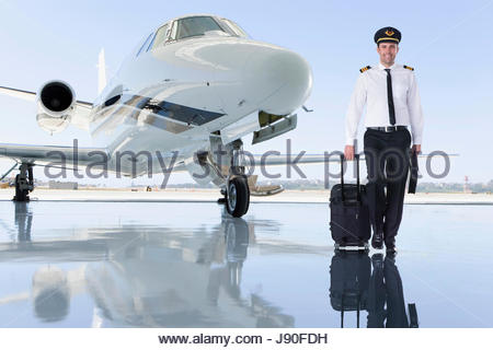 Pilot Of Private Jet Standing By Aircraft In Hangar - Stock-Bilder