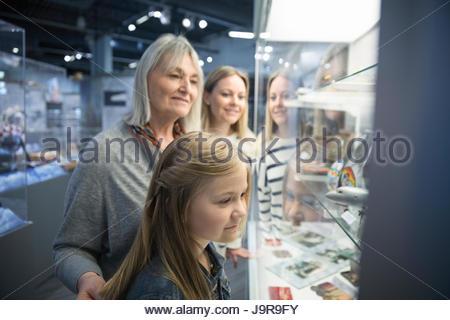 Female multi-generation family looking at exhibit artifacts in war museum - Stock-Bilder