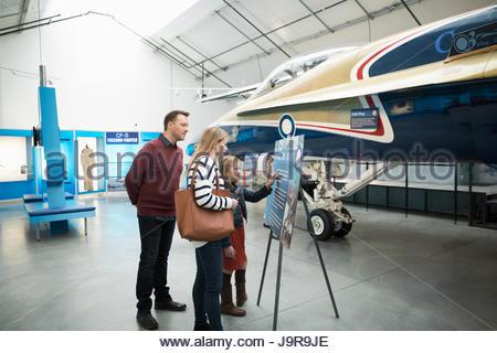 Family reading information board at Air Force airplane in war museum hangar - Stock-Bilder