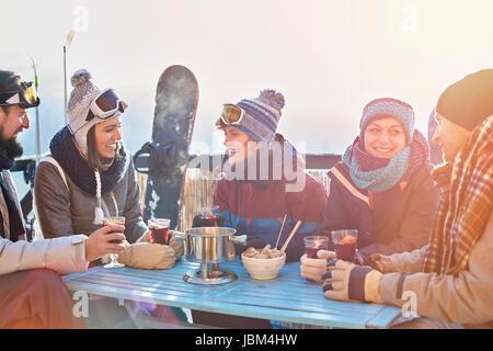 Snowboarder friends drinking cocktails on sunny balcony apres-ski - Stock-Bilder