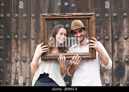 Portrait of mid adult couple, holding wooden frame in front of their faces, Mexico City, Mexico - Stock-Bilder