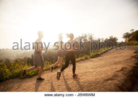 Three friends exercising outdoors, running uphill, in rural setting, rear view - Stock-Bilder