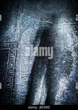 Scary shadow on old grave stone in church. Concept of death, crime and horror. - Stock-Bilder