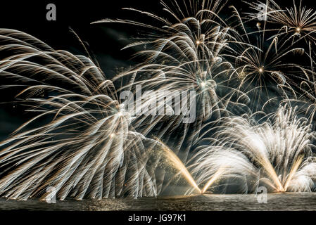 Details of Fireworks on the lakefront of Luino over the Maggiore Lake in a summer evening with blue sky and mountains - Stock Image