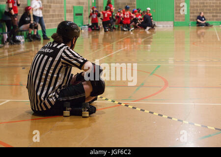Male roller derby ref sits crosslegged by the track waiting for a bout to begin - Stock Image