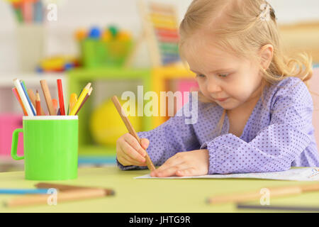 Cute little girl drawing with pencil  - Stock Image