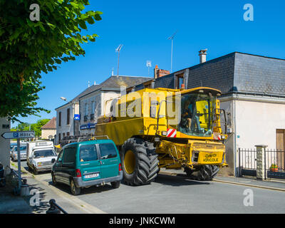 'New Holland TX66' combine harvester on narrow town street, Martizay, France. - Stock Image