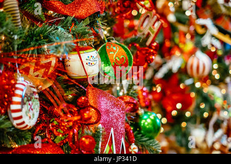 Various Christmas tree decorations and lights hanging on a traditional Christmas tree during the Christmas holiday - Stock Image