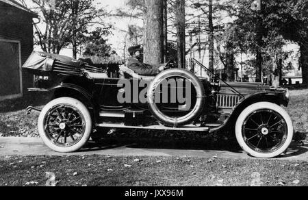 Full length landscape shot of Packard care with an African American chauffeur, outdoors, 1920. - Stock Image
