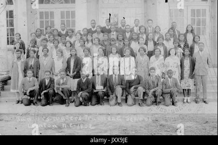 Full length portrait of a co-ed class of black students with two teachers, all students wearing uniforms; Winton, - Stock Image