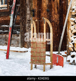 old farm door, nostalgic skis, slides, snow shovel, snowfall, - Stock Image