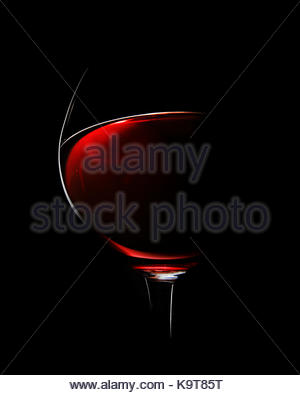 One Glass of Red Wine photographed with rim light against black background (focus on edge of glass) - Stock Image