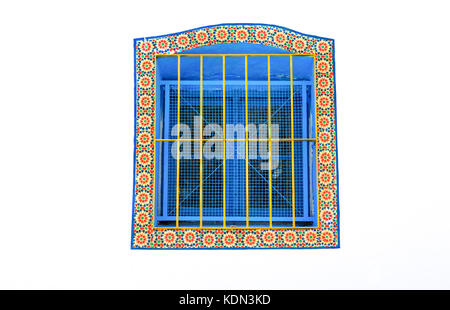Wrought iron window with glazed tiles all around, Tangier, Morocco - Stock Image