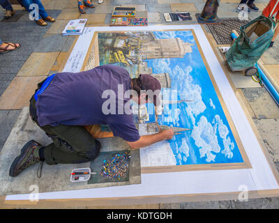 Pavement artist Didier Herry drawing with pastels, La Rochelle, France. - Stock Image