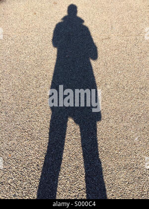A long shadow is cast on a sidewalk on a winter afternoon in Brooklyn, New York. - Stock Image