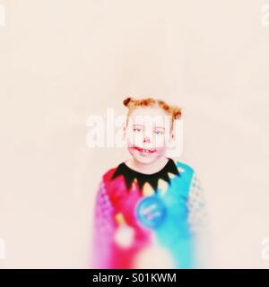 Young girl dressed as a clown with hair in buns. Colourful against a plain background - Stock Image