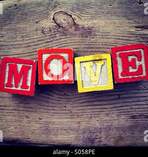It's a photo of two wood cubes toy with letters that form the word MOVE - Stock Image