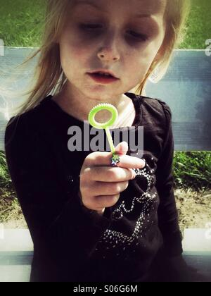 A child and her bubble making wand. - Stock-Bilder