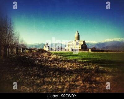 Georgian Orthodox Church and Caucuses mountain range - Stock Image