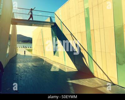 A boy striding across a bridge over an underpass - Stock-Bilder