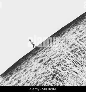Boy walking up hill - Stock Image