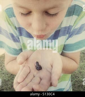 A child pretends to kiss a small frog. - Stock Image