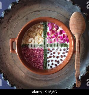 Yogurt with chopped walnuts, raisins, dried rose petals and dried mint. - Stock-Bilder