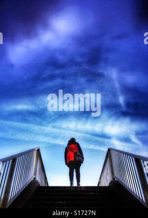 Graphic shapes and colours of woman in red coat on footbridge against a blue sky - Stock-Bilder