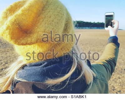 Pretty blonde with phone on beach. - Stock-Bilder