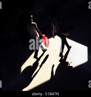 Passengers walk through a beam of light thrown on the platform of San Antonio metro station in Medellín, Colombia, - Stock Image