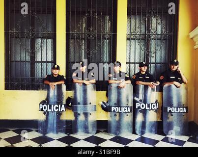 Five policemen standing in the shadow on Plaza de Armas in Lima, Peru - Stock Image