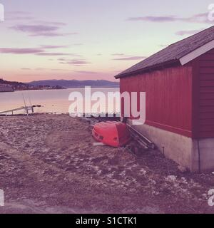 Red boathouse in the sunset, Romsdal, Norway - Stock Image