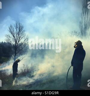 Two people in safety gear doing a controlled burning of a field in Minnesota, USA. - Stock-Bilder