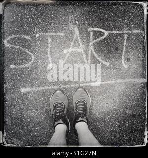 A runner stands at a spray painted start line. - Stock-Bilder