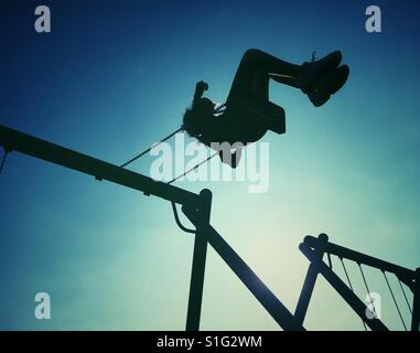 Young girl swinging high on playground swing in silhouette against the sun - Stock-Bilder
