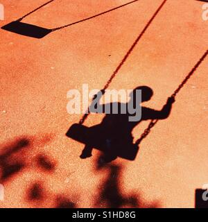 Shadow on playground floor of toddler on swing - Stock-Bilder
