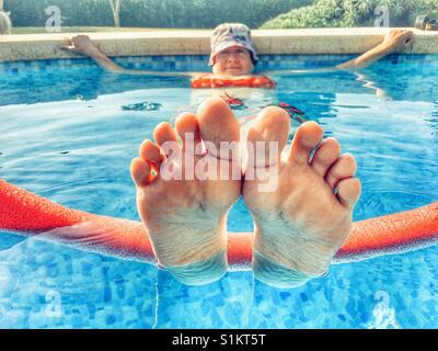 Woman in swimming pool, keeping cool in a heatwave - Stock Image
