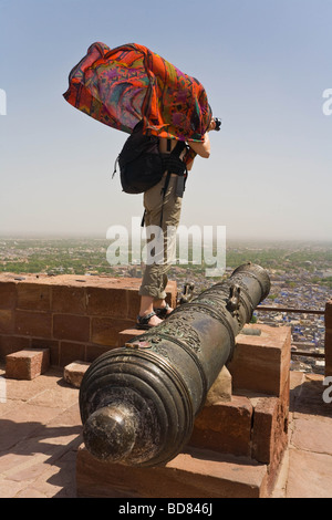 Tourist with flowing red shawl on a cannon in Jodhpur fort - Stock Image