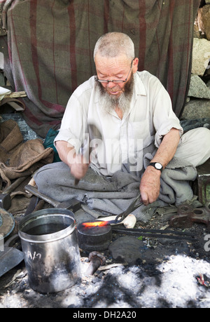 Indian blacksmith using exploded Pakistani artillery shell base as an anvil close to Pakistan border. Turkuk, Ladakh, - Stock Image