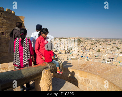 India, Rajasthan, Jaisalmer, Indian tourists enjoying view over city, from Fort Bastion, child sat on cannon - Stock Image