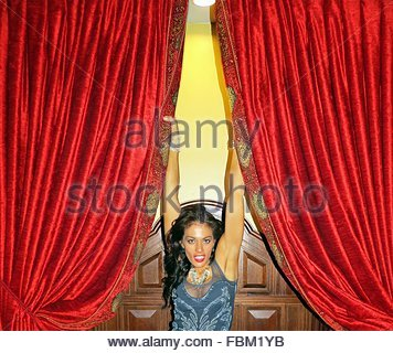 portrait of a smiling young woman against red curtains stock image