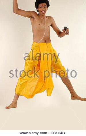 15ea7395bb South Asian Indian teenager boy wearing traditional silk dhoti Pitambar  thread holding pocket pc phone jump